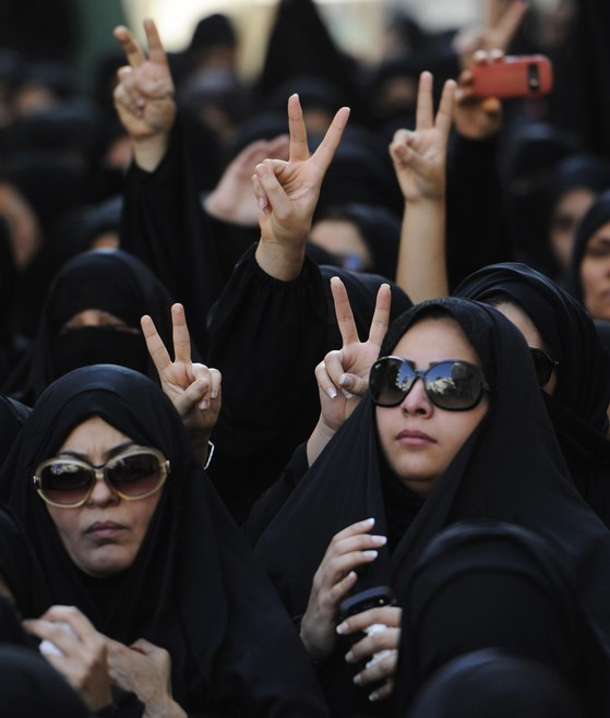 """[BAHRAIN-PROTESTS/KILLIN]Women show the victory sign during the funeral procession for Hussam al-Haddad, who died from birdshot wounds, in Muharraq, north of Manama, August 18, 2012. A 16-year-old protester was killed after what opposition activists in Bahrain said was a """"brutal attack"""" by security forces, but which the Bahrain government described as a defensive response to a petrol bomb attack on police. The government identified the dead youth as 16-year-old Hussam al-Haddad, and said he had been among"""