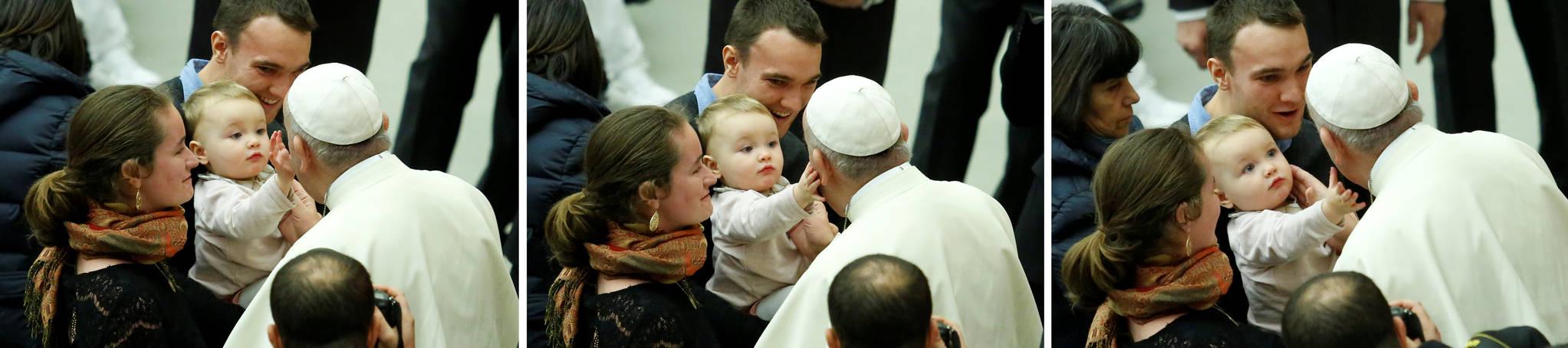 프란치스코 교황이 3일(현지시간) 바티칸 바오로 6세 알현실에서 열린 새해 첫 수요 일반알현에서 부모와 같이 온 어린아이가 자신의 볼을 어루만지자 같이 쓰다듬어 주고 있다.[로이터=연합뉴스]