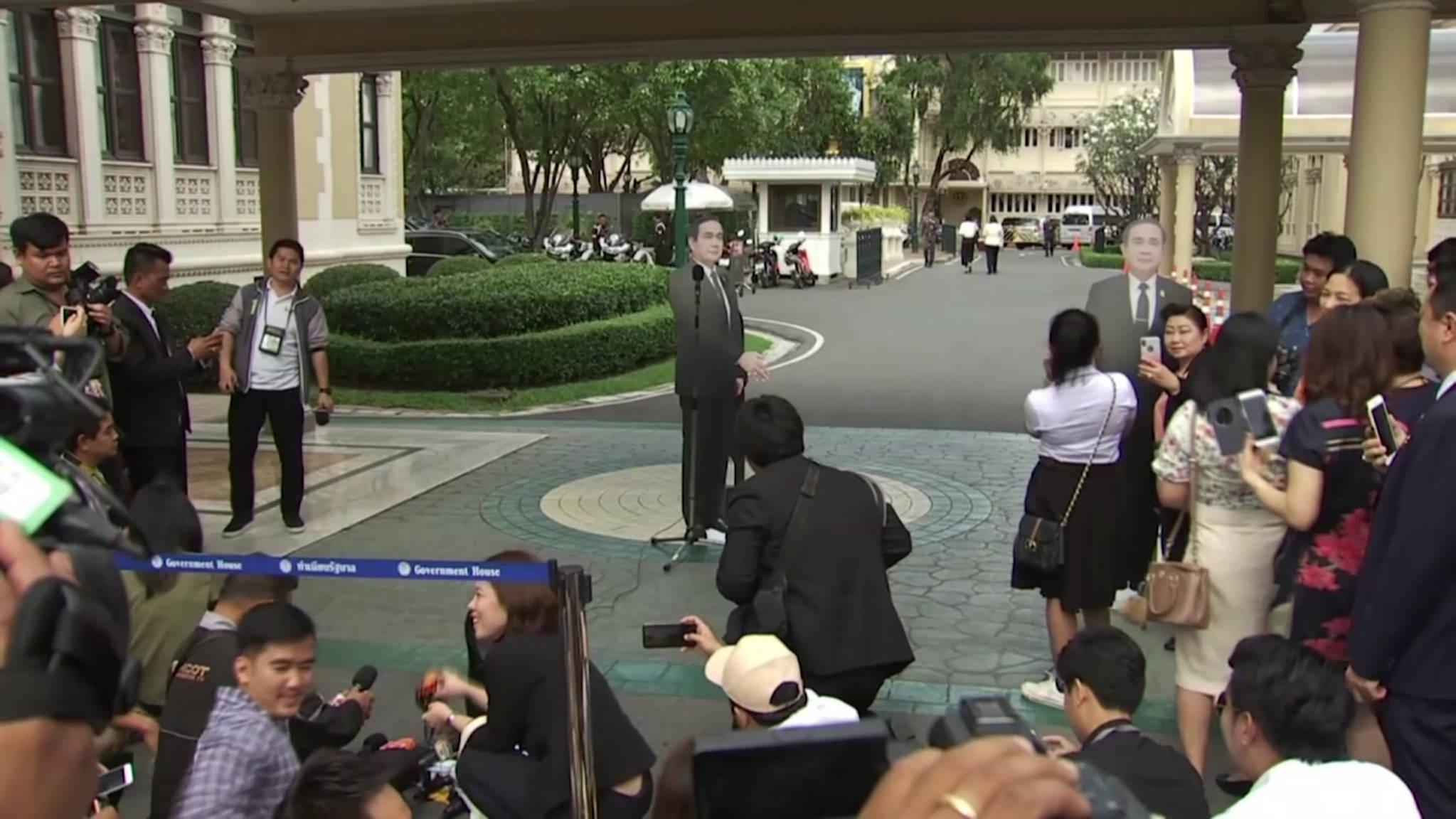 쁘라윳 태국 총리가 8일 방콕 총리관저에서 열린 브리핑에서 자신의 종인 인형을 세우두고 떠난 뒤 기자들이 황당해하고 있다.[AP=연합뉴스]
