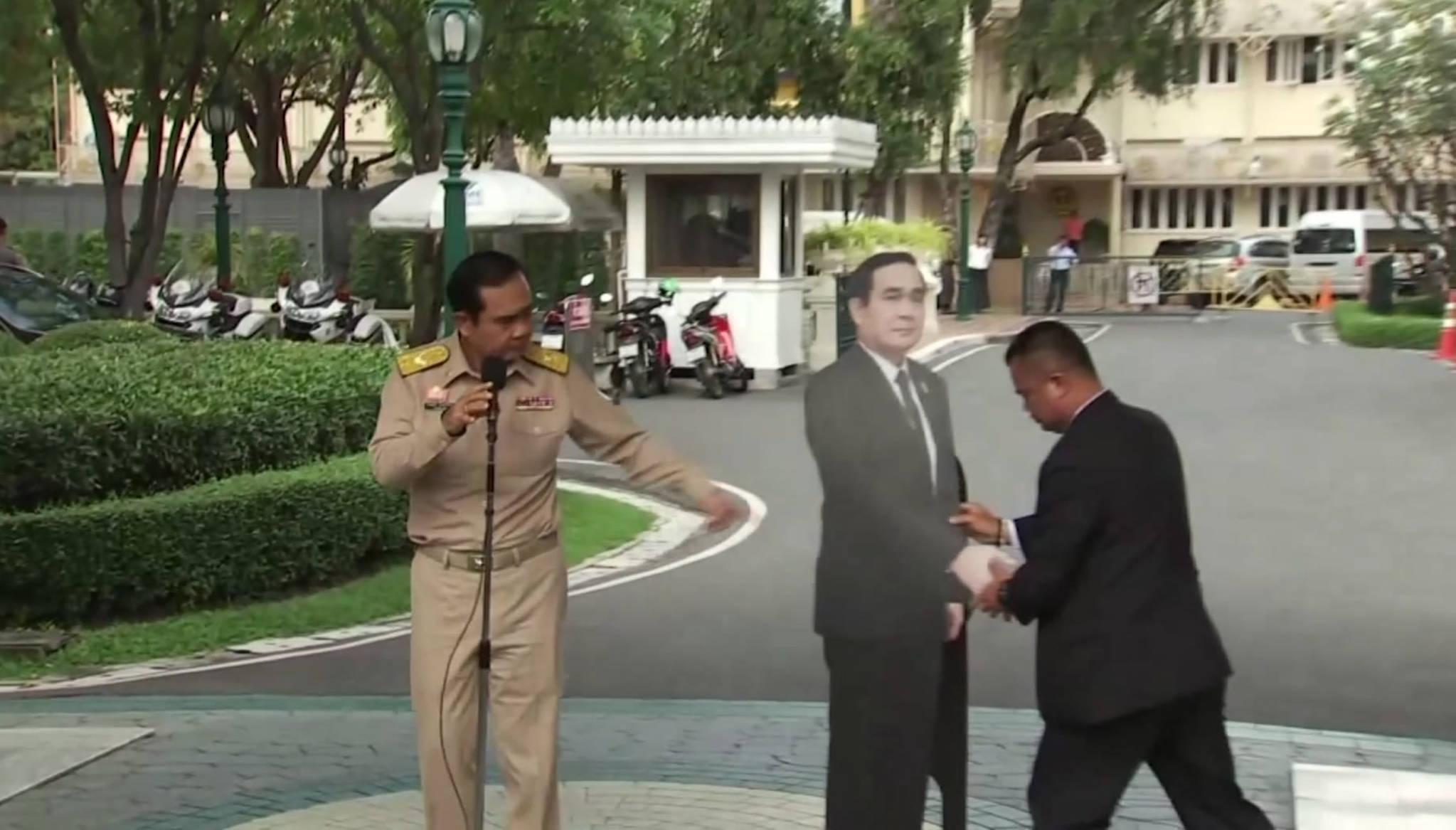 쁘라윳 태국 총리가 8일 방콕 총리관저에서 열린 브리핑에서 실물크기의 자신의 종이인형을 옆으로 가져오게하고있다.[AP=연합뉴스]