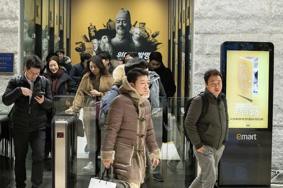 오후 5시가 되자 일제히 퇴근하는 이마트 본사 직원들. 오른쪽에 '정시퇴근을 위한 몰입도와 생산성 강화'라는 문구가 담긴 포스터가 보인다. 장진영 기자