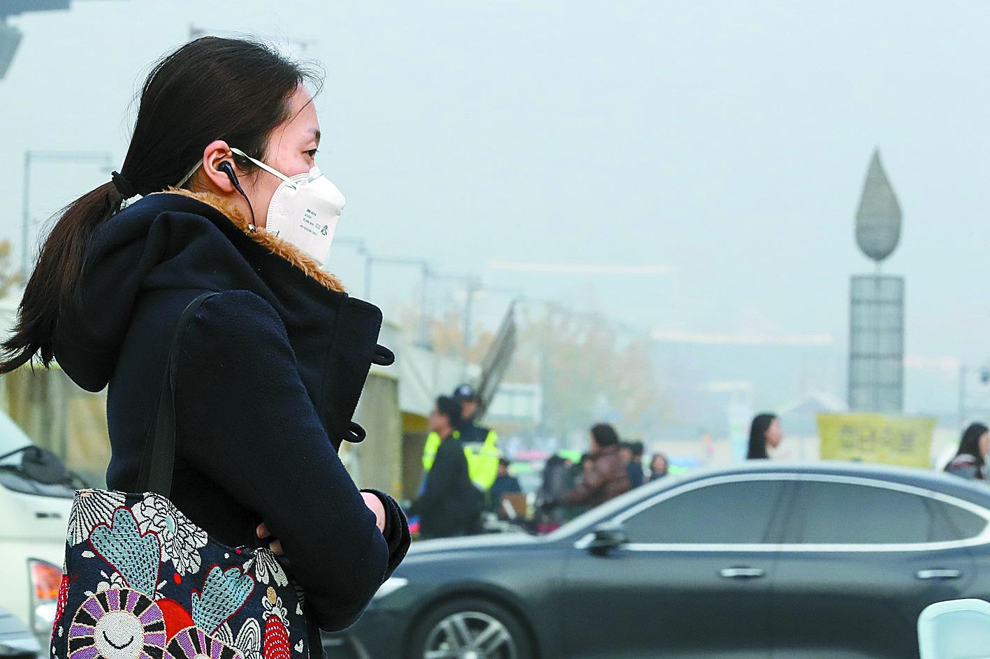 서울 광화문광장에서 바라본 도심 대기가 뿌옇다. 마스크를 쓴 시민이 출근길을 재촉하고 있다. [뉴시스]