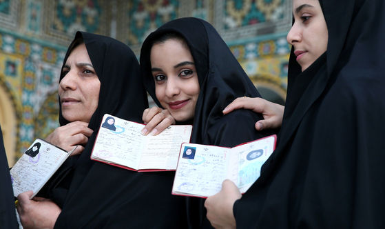 지난 2016년 2월 이란의 쿰에서 열린 총선 투표장에 나온 여성들이 신분증명서를 보이고 있다. [AP=연합뉴스]
