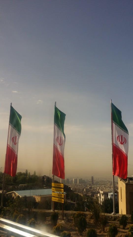 이란 수도 테헤란이 굽어보이는 언덕 위에 이란 깃발이 휘날리고 있다. 과거 군주제 시절 국기에서 군주를 상징하는 사자를 빼고 대신 아랍-페르시아 문자로 '알라'라는 글씨를 꽃봉오리처럼 디자인했다.