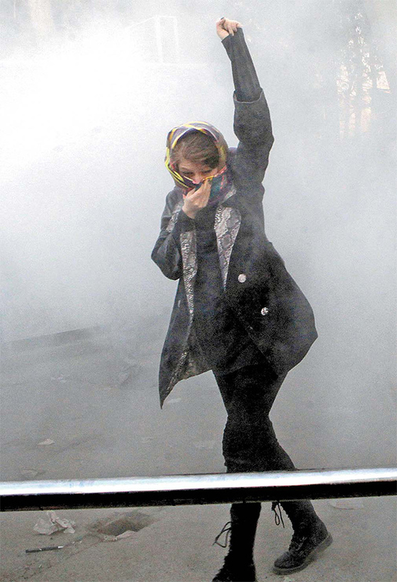 이란의 테헤란 대학 구내에서 지난달 30일 한 여학생이 최루탄 연기가 자욱한 가운데 반정부 구호를 외치고 있다. 지난 5일 테헤란에서 친정부 시위대가 미국 성조기를 불태우고 있다. [AP=연합뉴스]