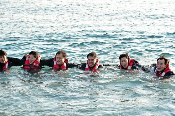 박경민 해양경찰청장(오른쪽 셋째) 등 해경 지휘부가 13일 부산 태종대 앞바다에서 잠수복을 입지 않고 바다에서 견디는 체험을 하고 있다. [사진 해양경찰청]