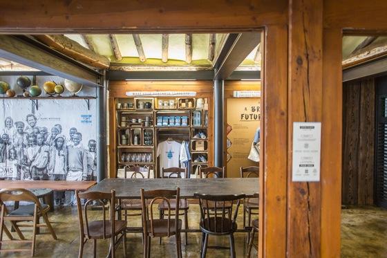 한옥 지붕의 서까래가 그대로 드러난 공간에서 커피와 함께 탐스의 어패럴이 판매되고 있다.[사진 탐스로스팅코]
