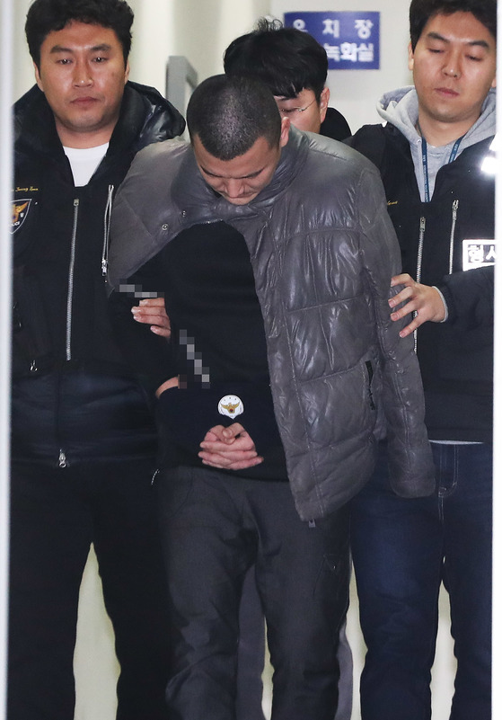 재가한 어머니의 일가족을 살해하고 뉴질랜드로 도피했다 국내로 송환돼 구속된 김성관(35)씨가 14일 오후 경기도 용인시 용인동부경찰서에서 조사를 받기 위해 이동하고 있다. [연합뉴스]