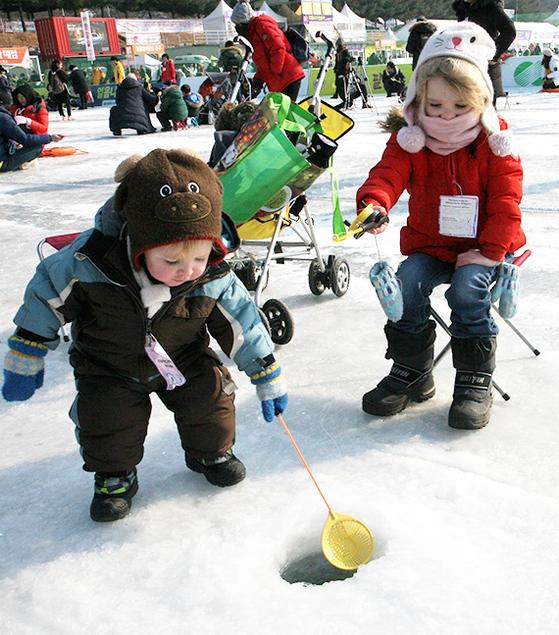 화천산천어축제를 찾은 외국인 어린이들이 14일 낚시를 즐기고 있다. 주말과 휴일 동안 총 36만5000명의 방문객이 축제장을 찾았다고 화천군청은 밝혔다. [뉴시스]