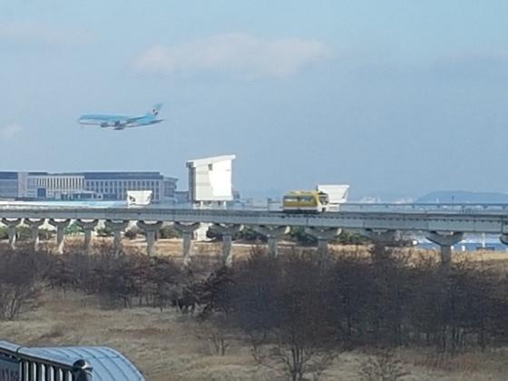 인천공항 자기부상열차가 선로를 달리고 있는 가운데 항공기가 착륙을 위해 낮게 날고 있다. 임명수 기자