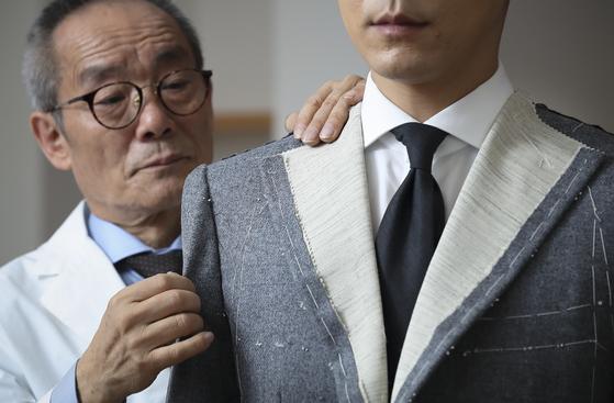 서울 강남구 청담동에 있는 비스포크 전문점 '레리치'의 마스터 테일러 장한종(73)씨가 고객의 몸에 맞춰 가봉을 하고 있다. 임현동 기자