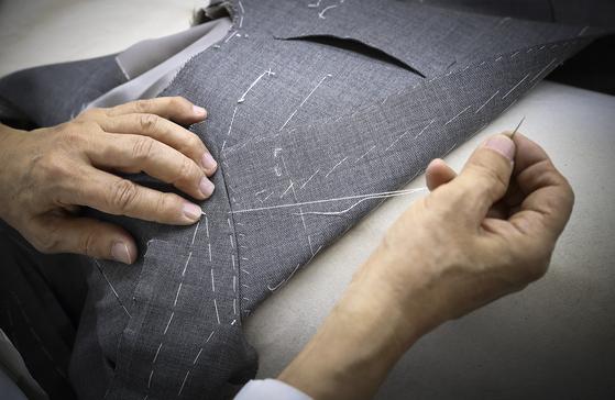 레리치 공방의 장인이 양복 재킷의 깃을 손바느질로 연결하고 있다. 재봉틀을 사용하는 것보다 부드럽게 연결되고 또 미묘한 차이까지 잡아낼 수 있다. 임현동 기자