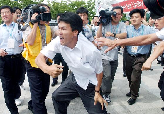 북 대표단 김강국, 2003년 대구서 보수단체와 몸싸움 벌인 기자