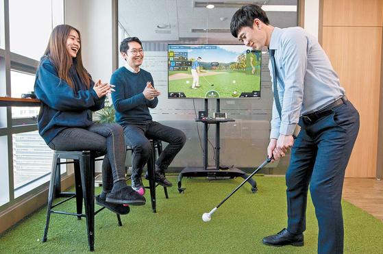 직장인들이 사무실 휴게 공간에서 파이골프를 연습봉에 장착한 뒤 스마트폰·TV와 연결해 골프 게임을 즐기고 있다.