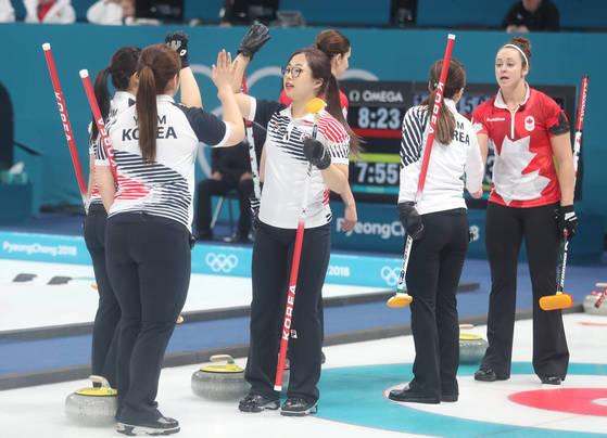 15일 강릉컬링센터에서 열린 한국과 캐나다 여자 컬링 예선 1차전에서 캐나다를 제압한 한국 선수들이 하이파이브하고 있다. [강릉=연합뉴스]