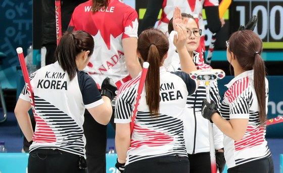 대한민국 컬링 국가대표팀이 15일 오전 강원도 강릉 강릉컬링센터에서 열린 2018 평창동계올림픽 컬링 여자 예선 세션 2 캐나다와의 경기에서 8대6으로 승리를 거둔 후 하이파이브를 하고 있다. [강릉=뉴스1]