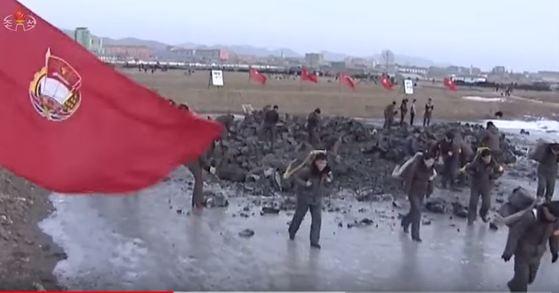 북한 주민들은 연초부터 김정은 새해 신년사 과업 관철을 위한 농촌거름전투 등에 총동원되며 거의 휴식 없이 달렸다. 거름생산을 위한 니탄운반에 동원된 주민들 [사진 조선중앙TV캡처]