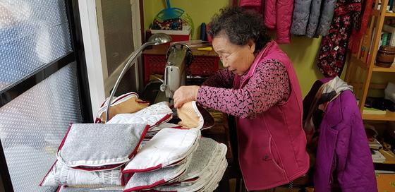 지난 12일 허우옥 할머니가 자투리 천을 이용해 주머니를 만들고 있다. 할머니는 주머니를 모두 무료로 기증하고 있다. 신진호 기자
