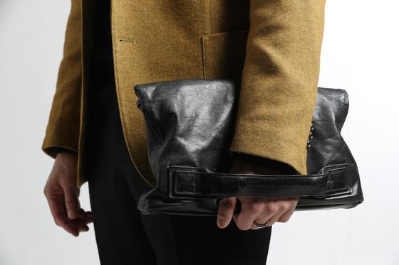 짐 들고 다니는 걸 좋아하지 않아 늘 여러 소지품을 넣을 수 있는 작은 클러치 형태의 가방 하나만 가지고 다닌다. 이것도 '일수가방' 디자인보다는 손잡이가 바닥쪽에 달린 디자인으로 감각을 살렸다.