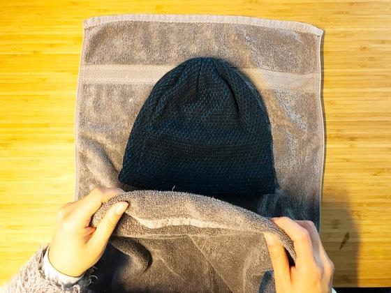 깨끗하게 헹궈낸 모자를 마른 수건 사이에 넣는다. 수건 한장을 반으로 접에 그 안에 넣으면 된다.
