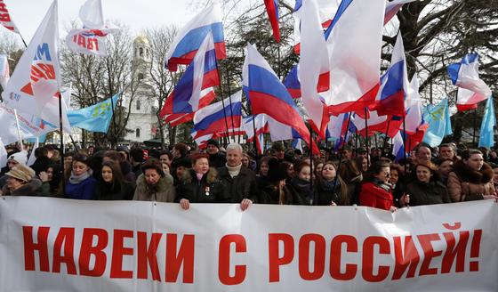 2014년 3월 16일 크림에서는 크림 반도의 미래를 결정하는 주민투표가 실시됐다. 당시 친러 시위대가 '러시아와 영원히'라고 쓰인 플래카드를 들고 시위하고 있다. [사진제공=Vostok-Photo]]