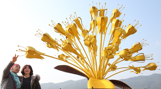 전남 구례군 산동면 '산수유 문화관'을 찾은 주민들이 황금색으로 만들어진 대형 산수유 꽃 조형물과 문화관 일대를 둘러보고 있다. 프리랜서 장정필