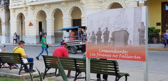 쿠바 산타클라라의 광장에서 휴대전화 이용자들이 인터넷에 접속 중이다. 오른쪽은 공산당 선전 간판.