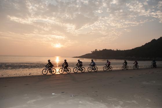 전남 신안군 자은도에서 관광객들이 자전거를 타고 노을 물든 해변을 달리고 있다. [사진 신안군]