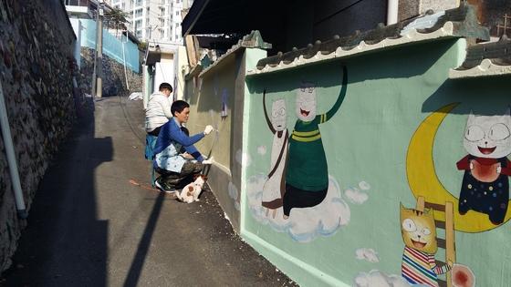 지난해 11월 강원도 춘천시 효자1동 벽화마을에서 작가들이 인기 애니메이션 '구름빵'의 고양이 캐릭터를 그리고 있다. [사진 효자1동 주민자치센터 ]
