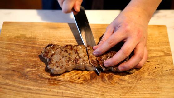 구운 고기는 한입 크기로 썬다.