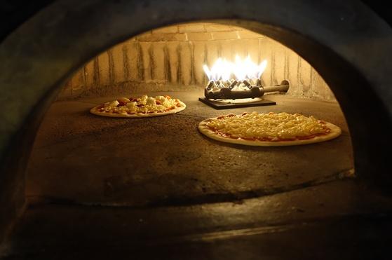 화덕에 들어간 지 12초 후. 피자에 올린 치즈가 녹기 시작했다.
