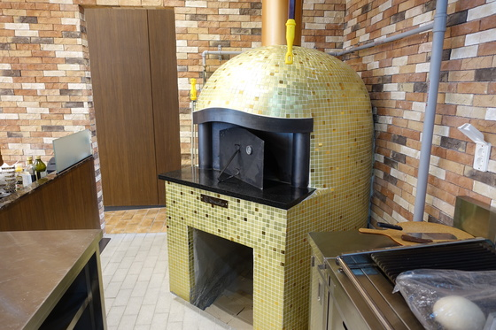 금빛 타일로 장식한 'R.ENA' 레스토랑의 가스 화덕. 피자와 팬에서 1차 구운 스테이크를 굽는다.