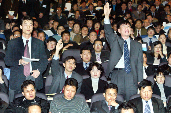 삼성전자 주주총회에서 소액주주 운동을 펴는 참여연대 관계자들이 손을 들어 발언권을 요구하고 있다.