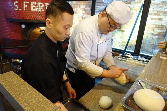 1차 발효를 마친 빵 반죽을 오븐에서 2차 발효하기 전에 치대고 있다.