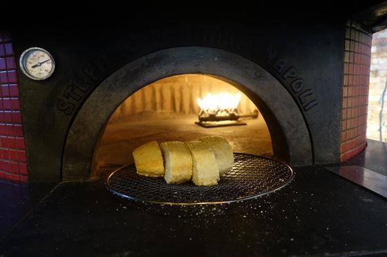 식전빵을 테이블에 내가기 앞서 피자화덕에서 데우고 있다.