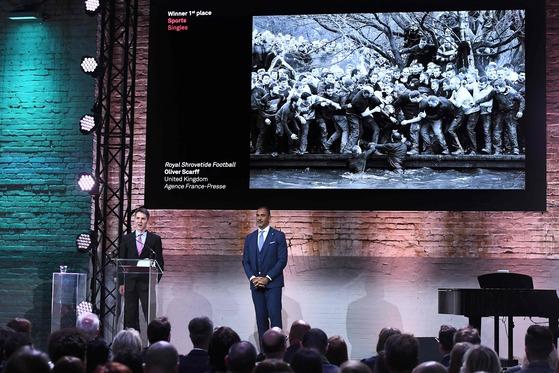 영국의 AFP 사진기자 올리버 스카프(왼쪽)가 12일(현지시간) 암스테르담에서 수상 소감을 발표하고 있다. 그는 영국에서 매년 봄 열리는 전통축구의 한 장면으로 스포츠 부문 1위를 차지했다.[AFP=연합뉴스]