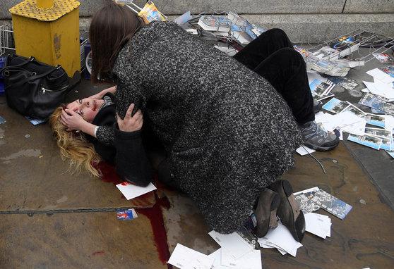 '올해의 사진' 후보로 올랐던 런던테러 현장 직후 모습. 작년 3월 테러가 발행한 런던의 웨스트민스터 다리에서 한 행인이 부상당한 여인을 돌보고 있다. 차량을 몰고 행인들을 향해 돌진한 테러로 5명이 사망하고 많은 사람이 부상을 당했다.[로이터=연합뉴스]