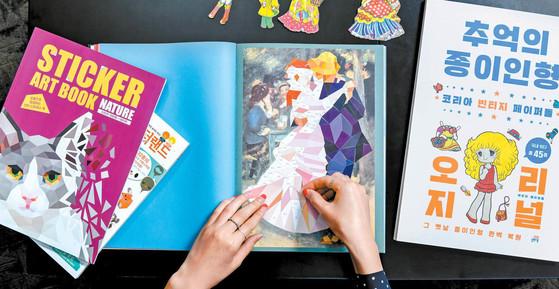 조각 스티커를 하나씩 붙이며 작품을 완성할 수 있는 스티커 아트북이 인기를 끌고 있다/ 가위로 종이를 잘라 인형 놀이를 할 수 있는 책