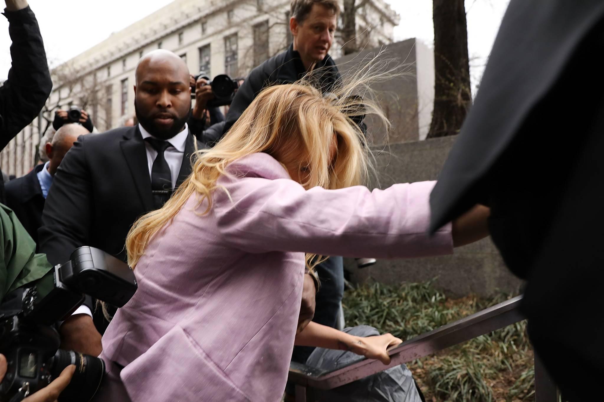 법원에 출석하던 스토미 대니얼스가 둘러쌓인 취재진에 떠밀려 넘어지려하자 난간을 붙잡고 있다. [AFP=연합뉴스]