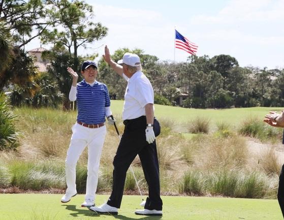 도널드 트럼프 미국 대통령이 지난해 2월 플로리다 골프장에서 아베 신조 일본 총리(왼쪽)와 골프 라운딩 도중 하이파이브를 하고 있다. [연합뉴스]