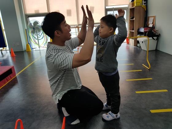 박지성 재활치료사와 하이파이브를 하고 있는 송준민군.