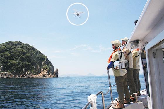 무인도의 염소 포획작전에 투입된 드론(원 안)이 섬을 향해 날아가고 있다. [사진 국립공원관리공단]