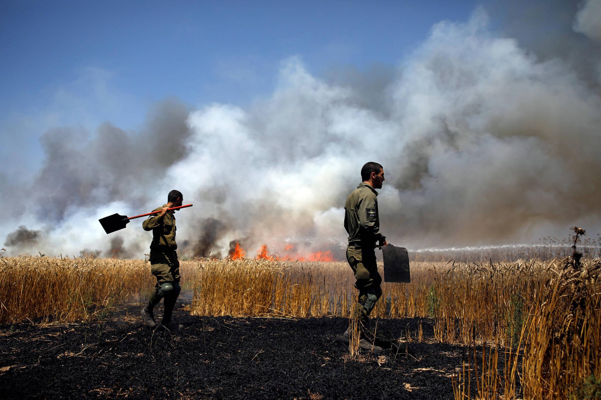 이스라엘 군인들이 14일 가자지구 국경에서 발생한 화재를 진압을 하고 있다. [로이터=연합뉴스]