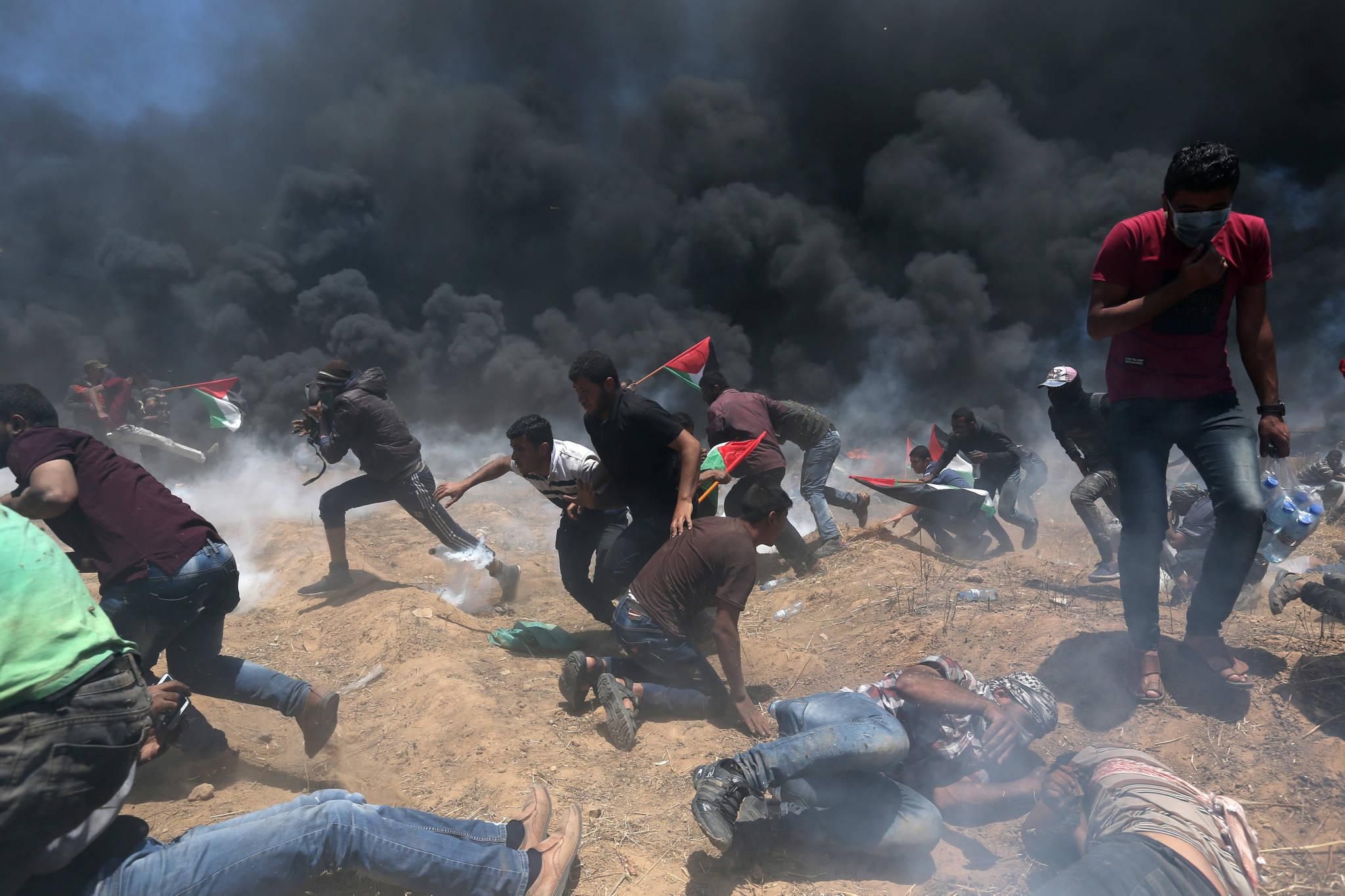 팔레스타인 시위대가 14일 가자지구에서 이스라엘 군이 최루탄을 발사하자 도망치고 있다. [로이터=연합뉴스]