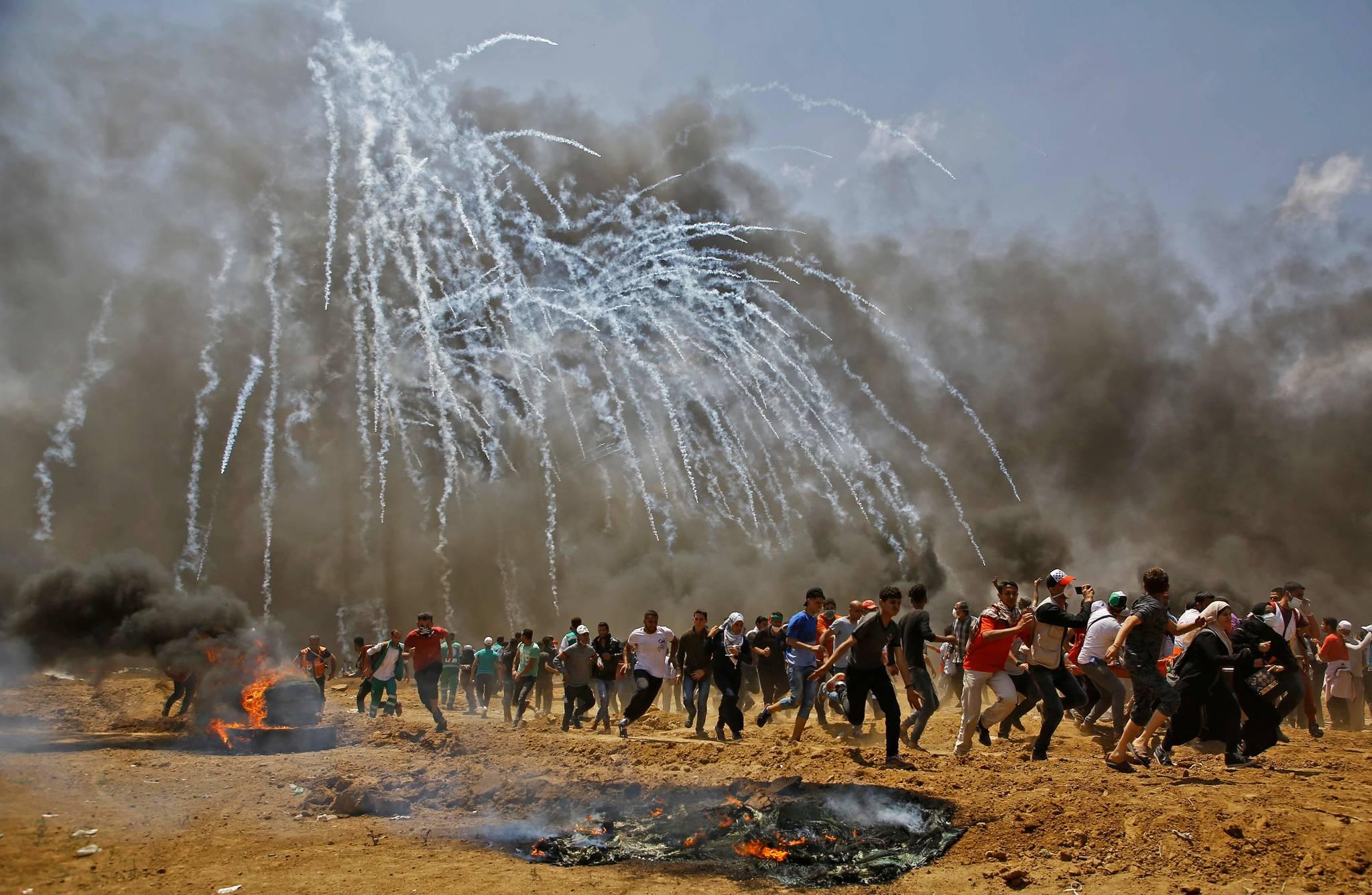 미국대사관의 예루살렘 이전에 반대하는 팔레스타인들이 14일(현지시간) 가자지구에서 이스라엘 군이 쏜 최루탄을 피해 도망치고 있다. [AFP=연합뉴스]