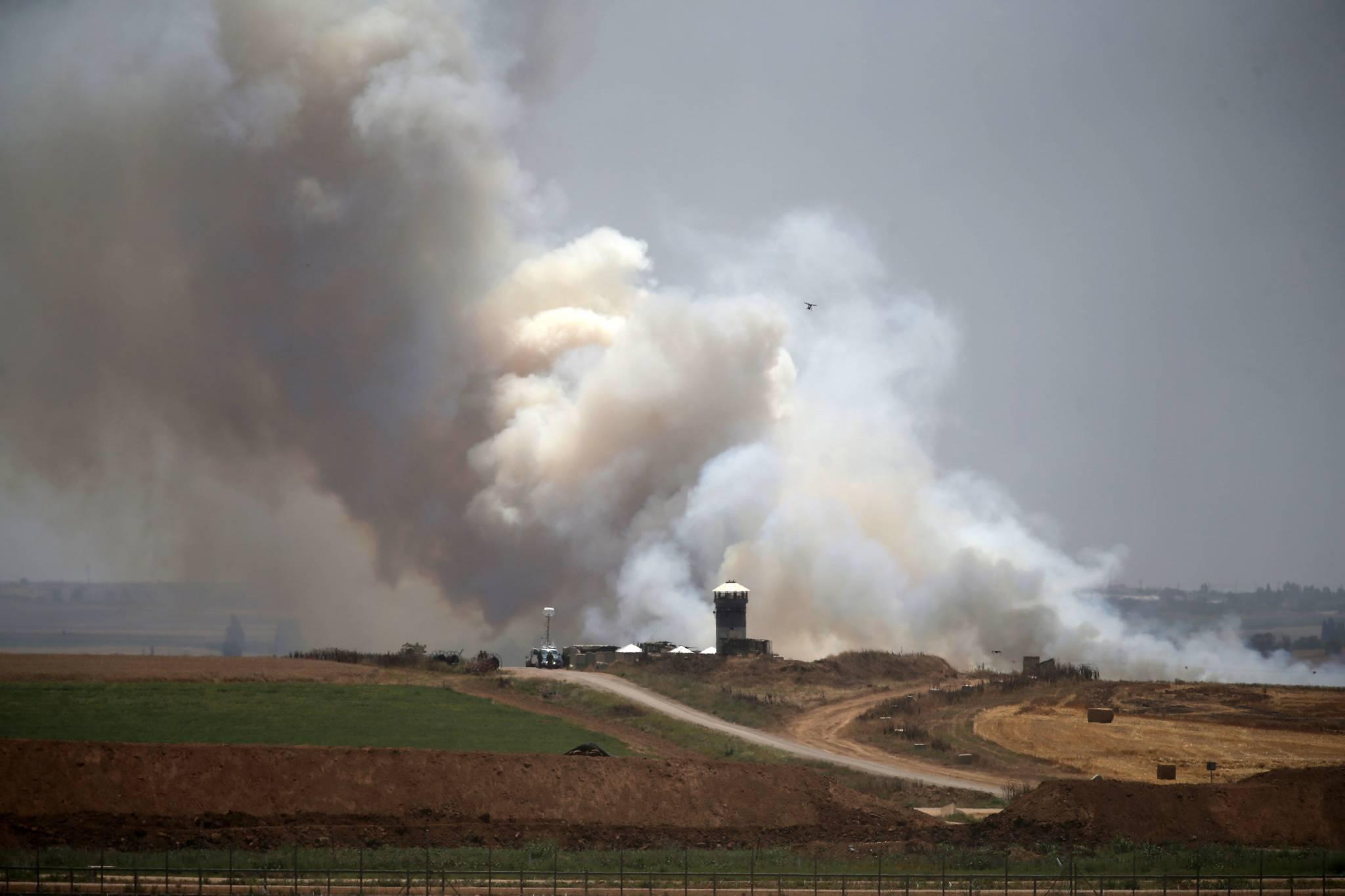 14일 가자지구에서 팔레스타인들이 연에 매달아 날려 보낸 폭탄이 이스라엘 진영에 떨어져 연기가 피어오르고 있다. [AFP=연합뉴스]