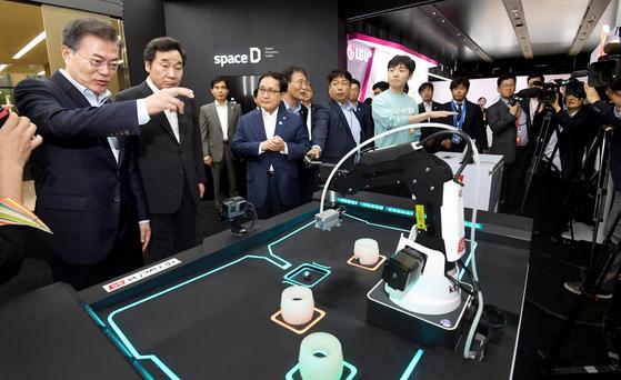 문재인 대통령이 17일 서울 마곡 연구개발단지에서 열린 '2018 혁신성장 보고대회'에 참석해 5G를 이용한 동작 인식 로봇을 직접 조작해 보고 있다. [김상선 기자]
