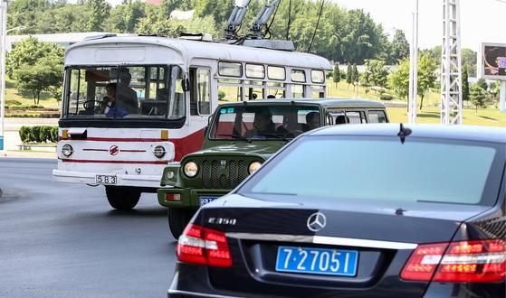 지난달 31일 평양 시내에 오래된 버스와 고급 승용차가 보인다. [타스=연합뉴스]