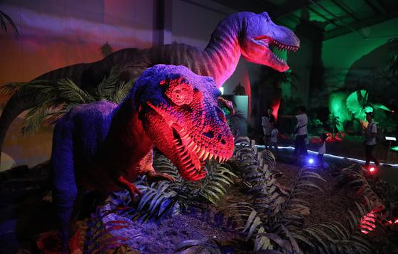 공룡곤충 전시관 내 어둠 속에서 으르렁 거리는 공룡 모형. [중앙포토]