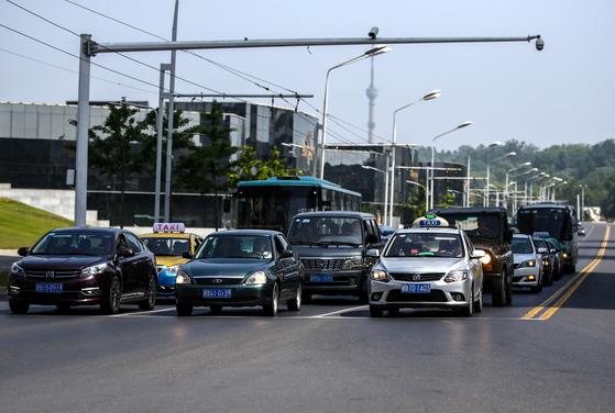 지난달 31일 평양 시내에서 택시 등 차량이 신호를 기다리며 대기하고 있다. [타스=연합뉴스]